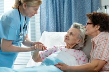 older female patient in hospital bed receiving care