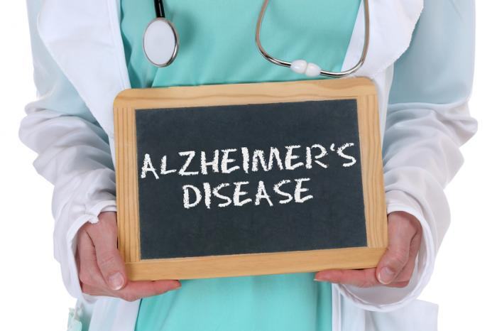 [A doctor holding a sign with Alzheimer's disease written on it]