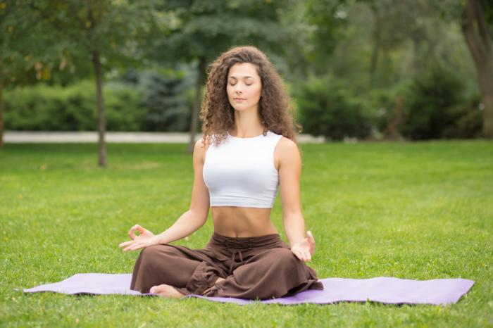 A woman is meditating in a park.