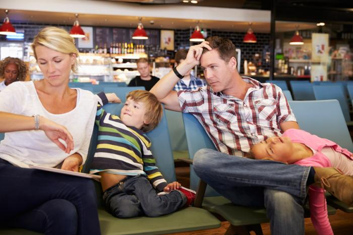 [Family waiting for a delayed flight in a departure lounge]