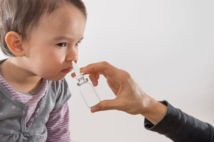 [A child being given a nasal spray vaccine]