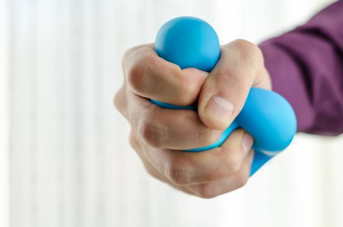 [A man squeezing a stress ball]
