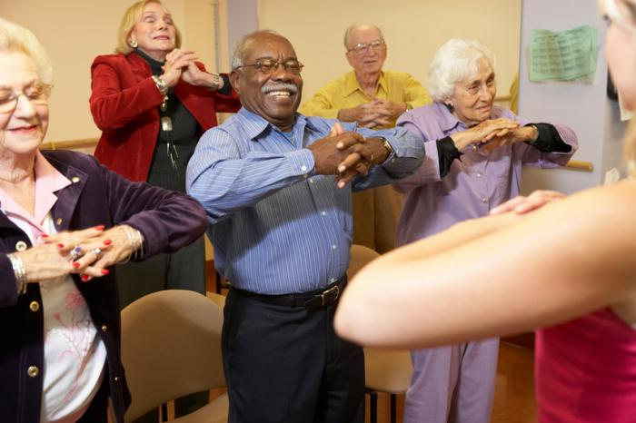 [Happy older adults exercising]