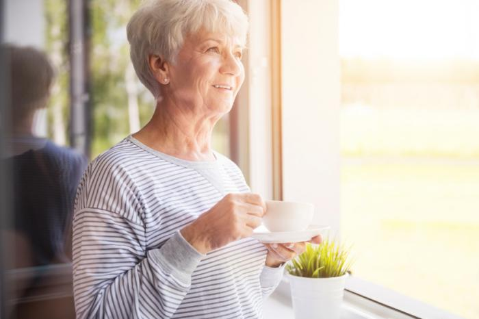 [An older woman looking out of the window ad holding a hot drink]