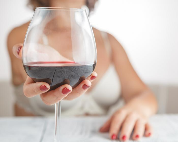 [Woman holding glass of red wine]