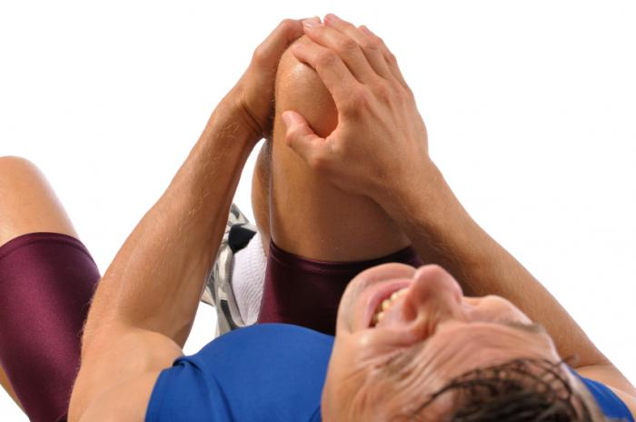 Man clutching painful knee
