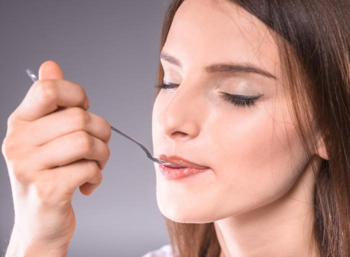 A woman with closes eyes eats some food from a metal spoon