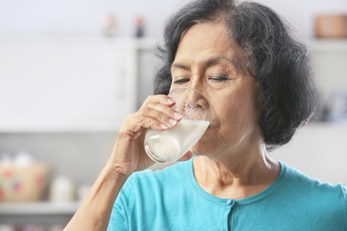 [An older lady drinking a glass of milk]