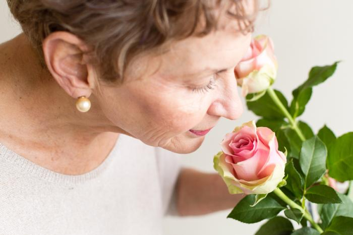 [An older woman smelling a pink rose]