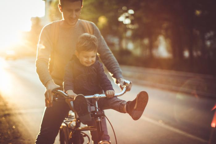 [Dad riding bike with his son]
