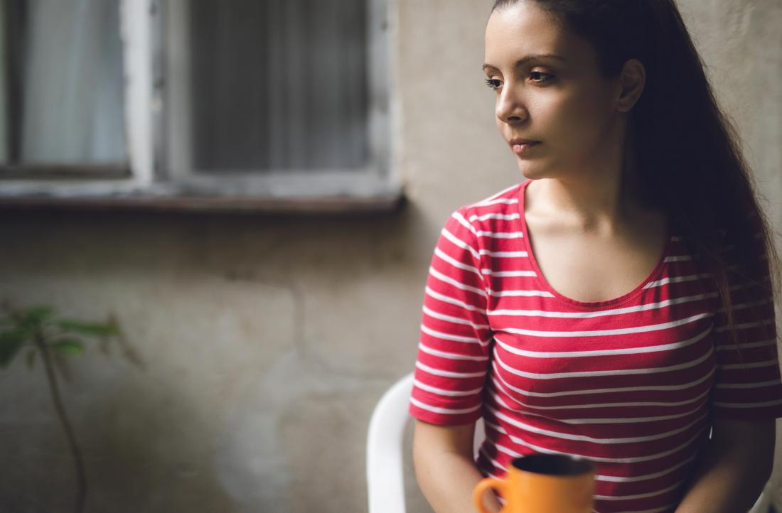 Depressed sad woman sitting on chair with hot drink