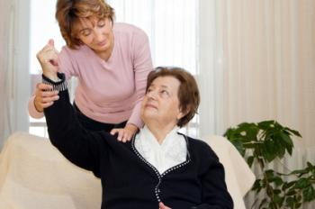 carer helping patient move arm