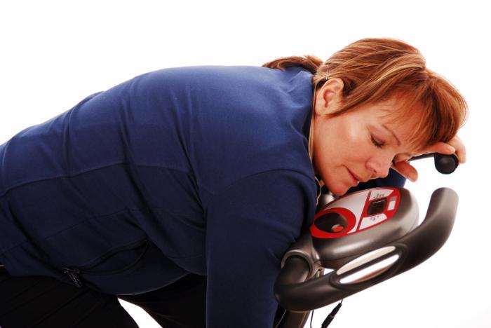[femme endormie sur un vélo d'appartement]
