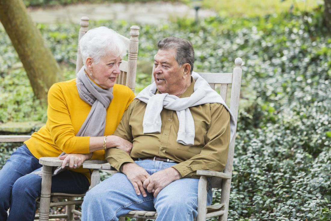 Senior couple sitting on wooden chairs in garden having conversation.