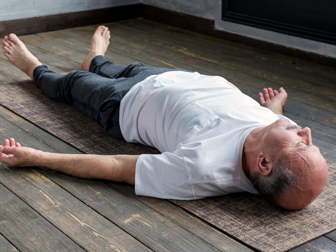a senior man doing Corpse pose or Savasana as part of yoga routine for fibromyalgia