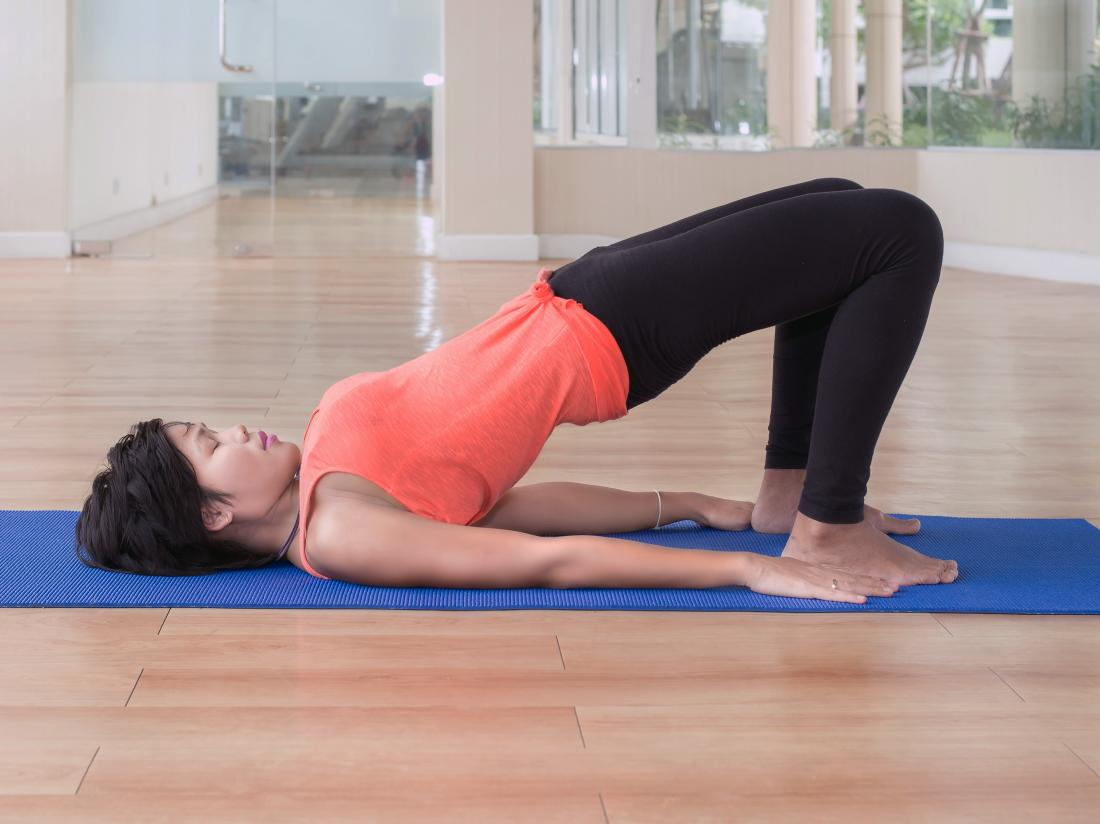 a woman doing bridge pose or Setu Bandha Sarvangasana as part of yoga routine for fibromyalgia