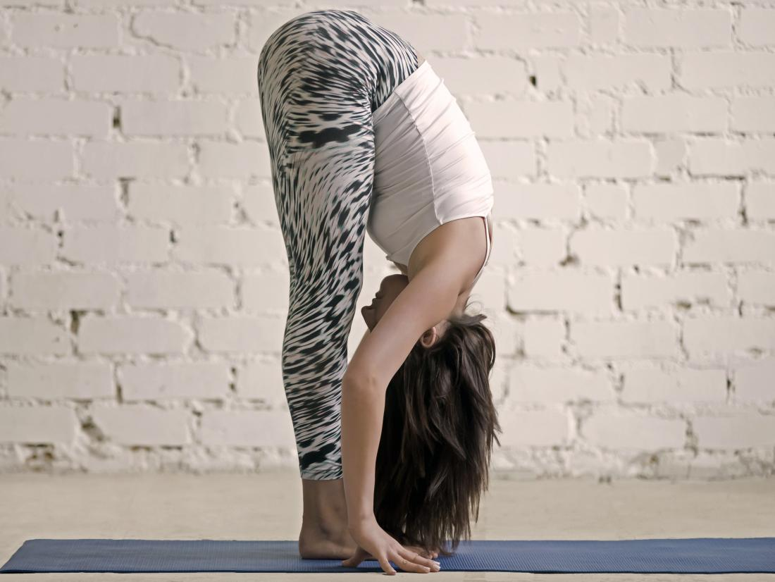 a woman doing Standing Forward Bend or Uttanasana as part of yoga routine for fibromyalgia