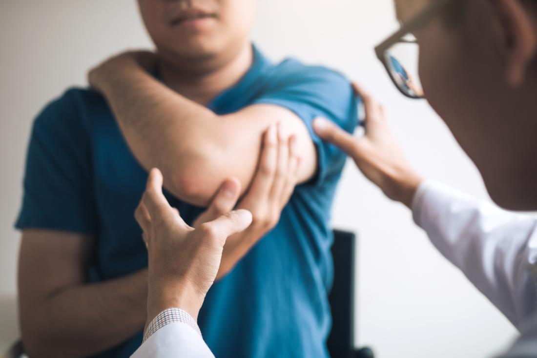 a doctor examining the elbow of a patient because it is one of the fibromyalgia tender points