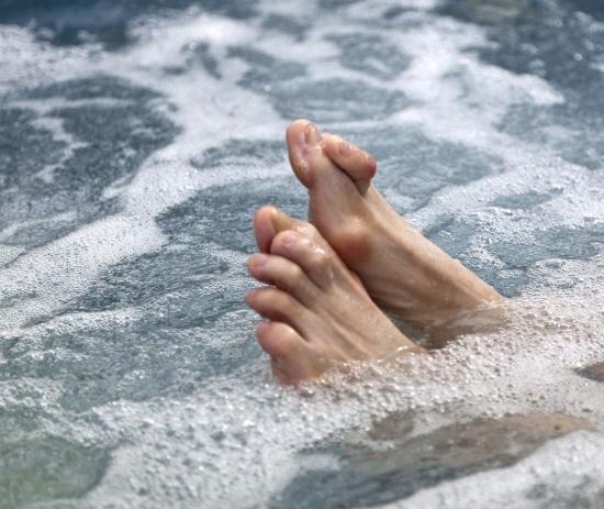 Photograph of feet with hammertoe soaking in water.