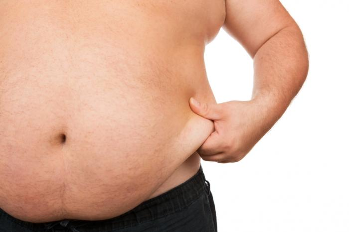 man pinching abdominal fat