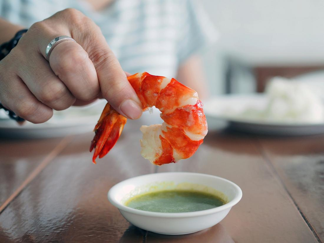 a woman dipping shrimp into a dip which might or might not be high in cholesterol