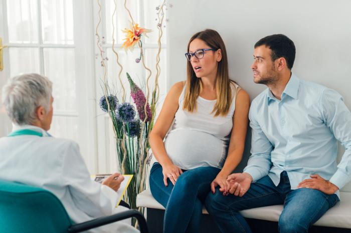 [pregnant couple discussing with doctor]