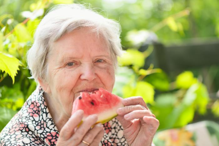 [An older woman eating watermelon]