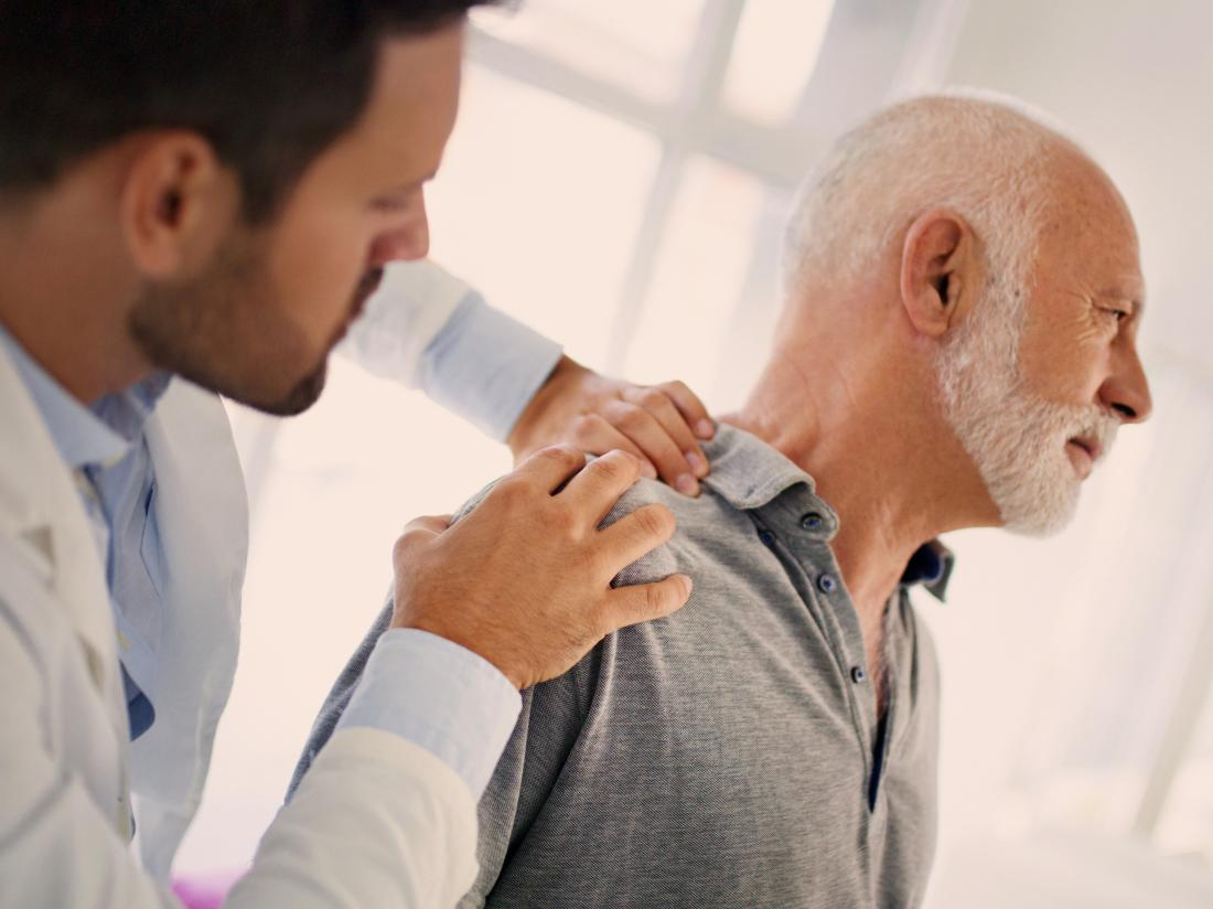 a doctor examining a mans shoulder pain to make sure he does not have lung cancer.