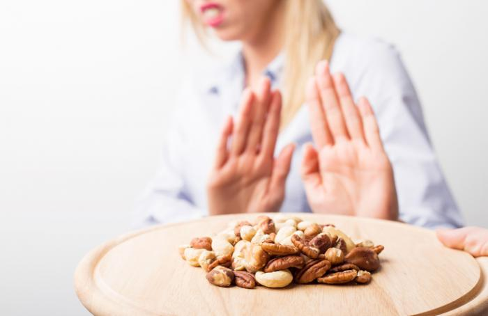 [woman vehemently refusing nuts]
