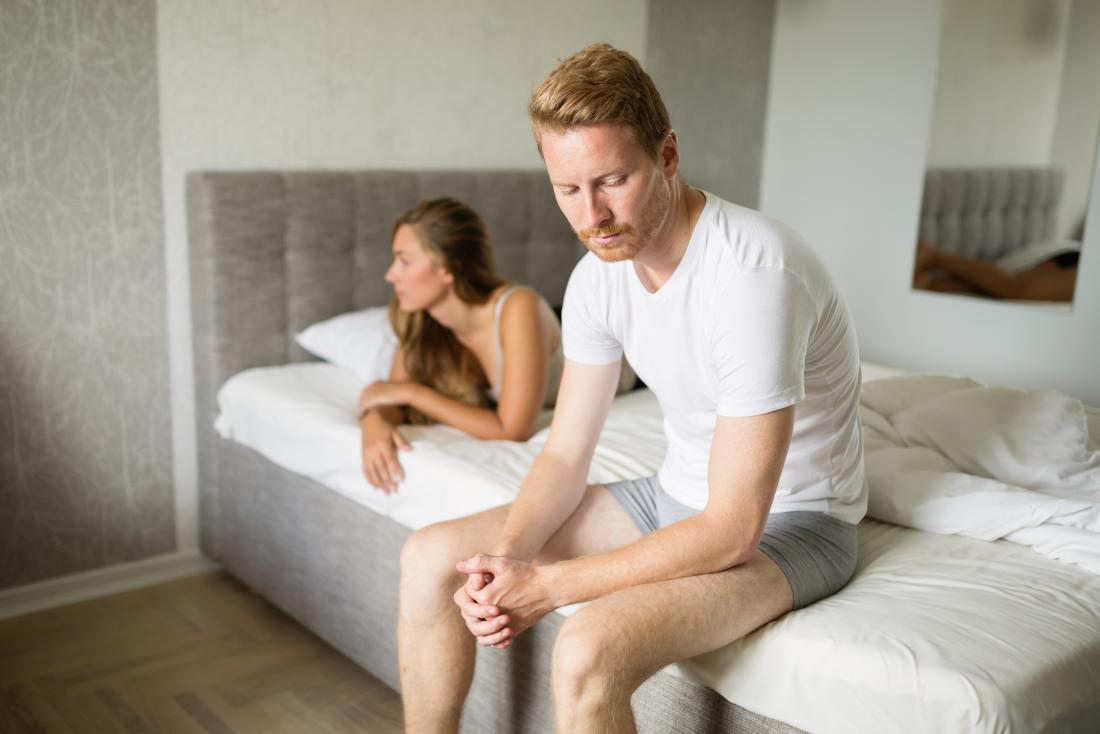 Man with erectile dysfunction sitting on edge of bed with woman lying looking the other way.