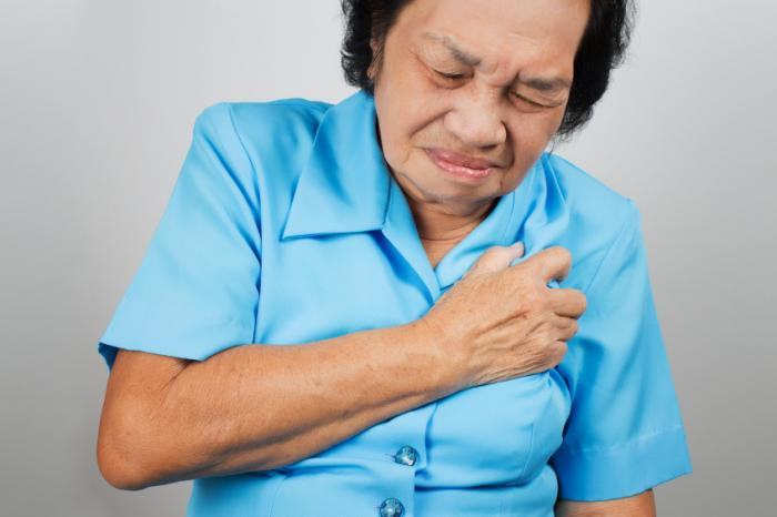 woman clutching left side of upper chest