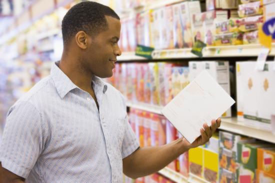 un homme qui lit l'étiquette de la valeur nutritionnelle sur le paquet