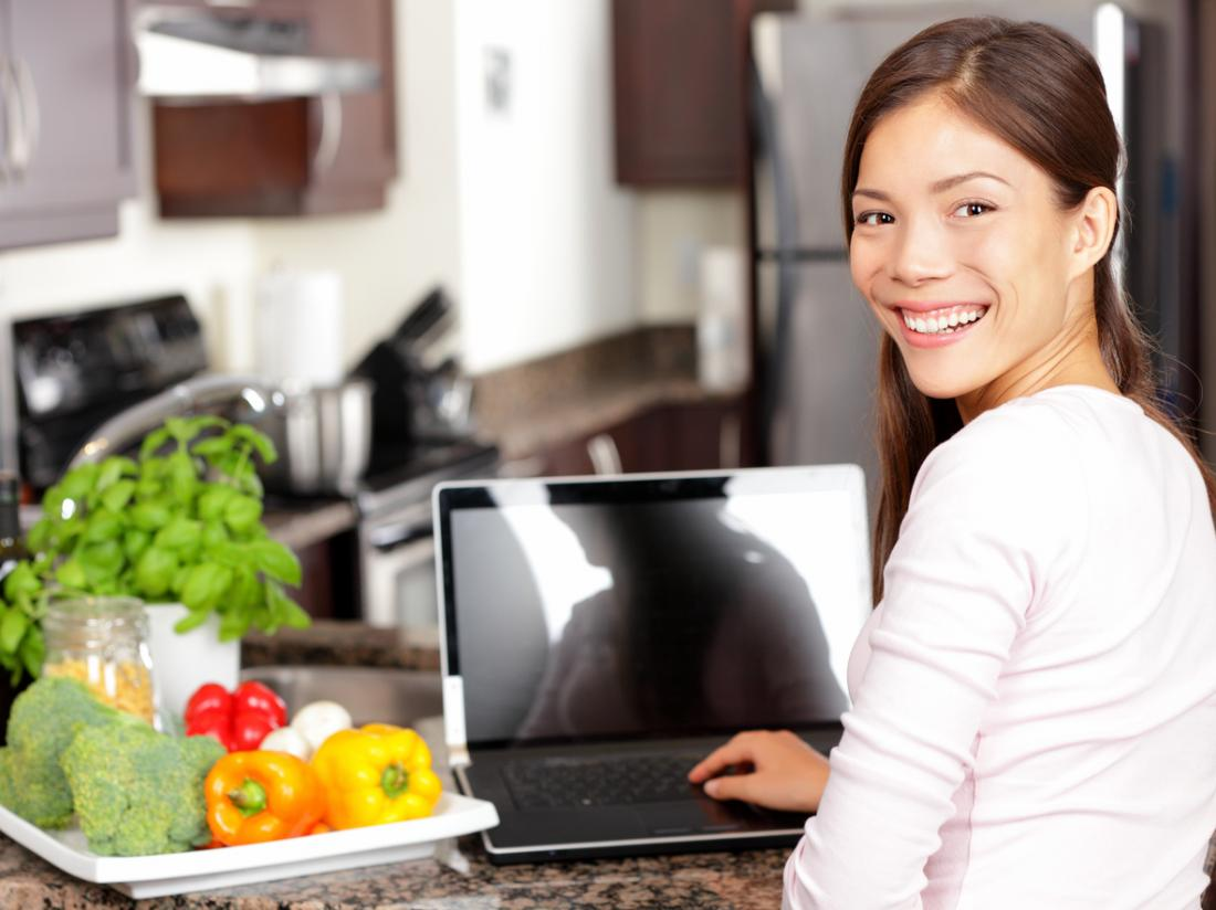 [young woman on her laptop in the kitchen ]
