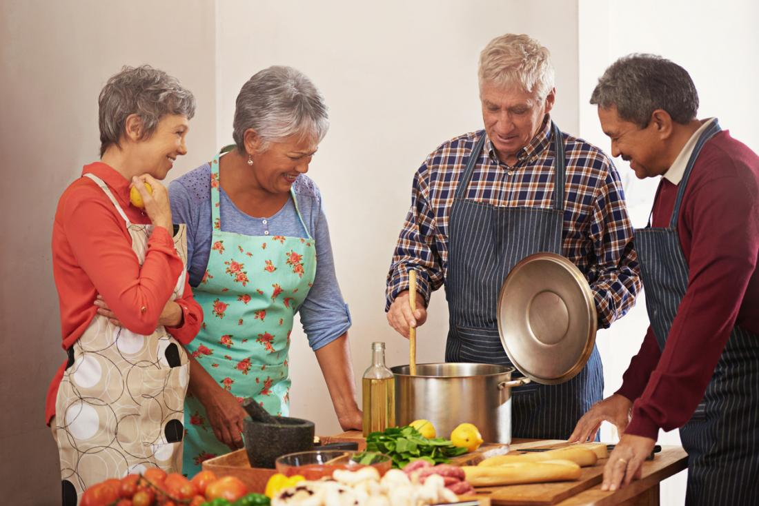 [four older people cooking together]