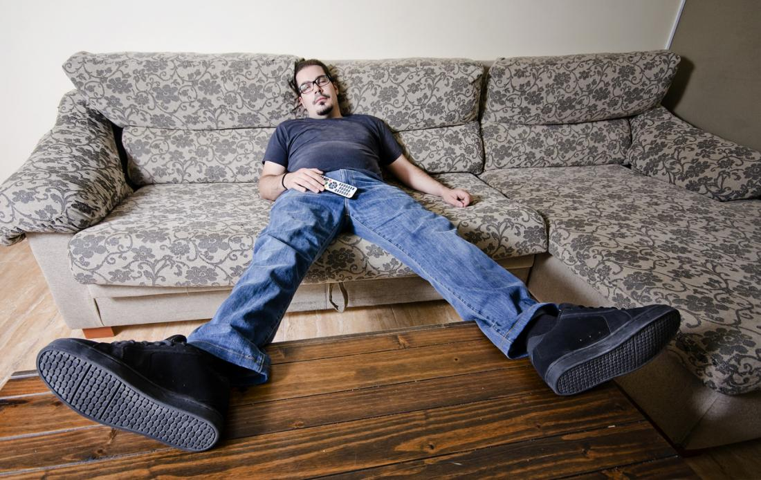 [A man lounging on a sofa]