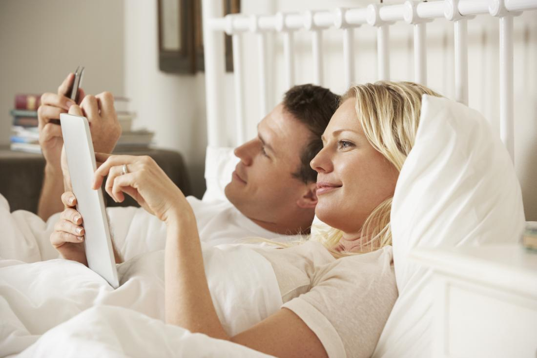 [couple using digital tablet and mobile phone in bed]