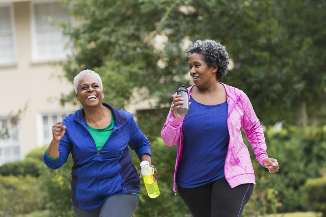 [two older women having a laugh while exercising outdoors]