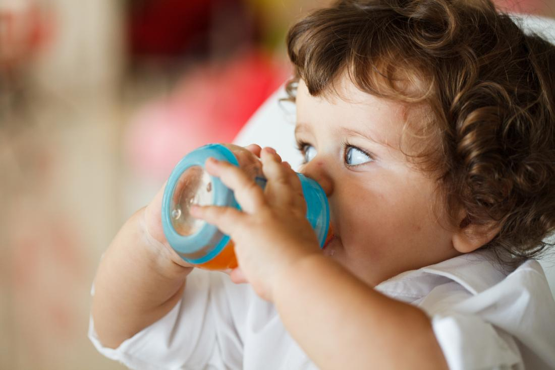 [A baby drinking out of a bottle]