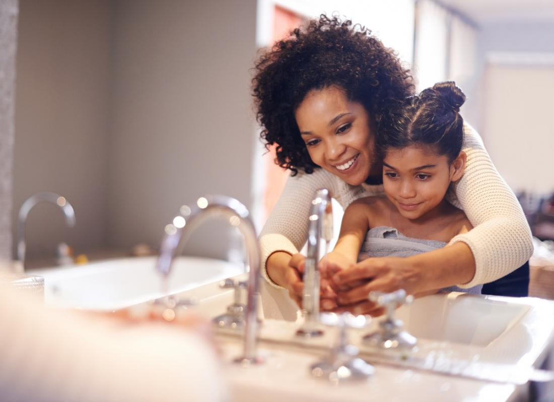 [mother helping her child wash hands]