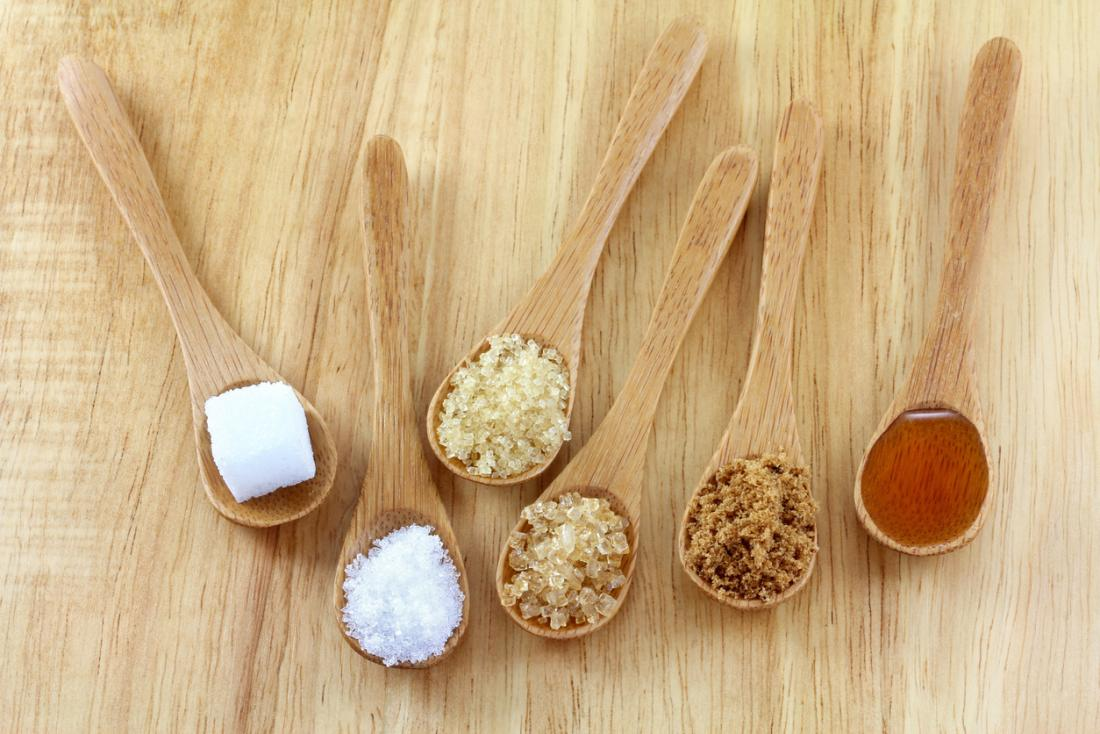 [variety of sugars on display in wooden spoons]