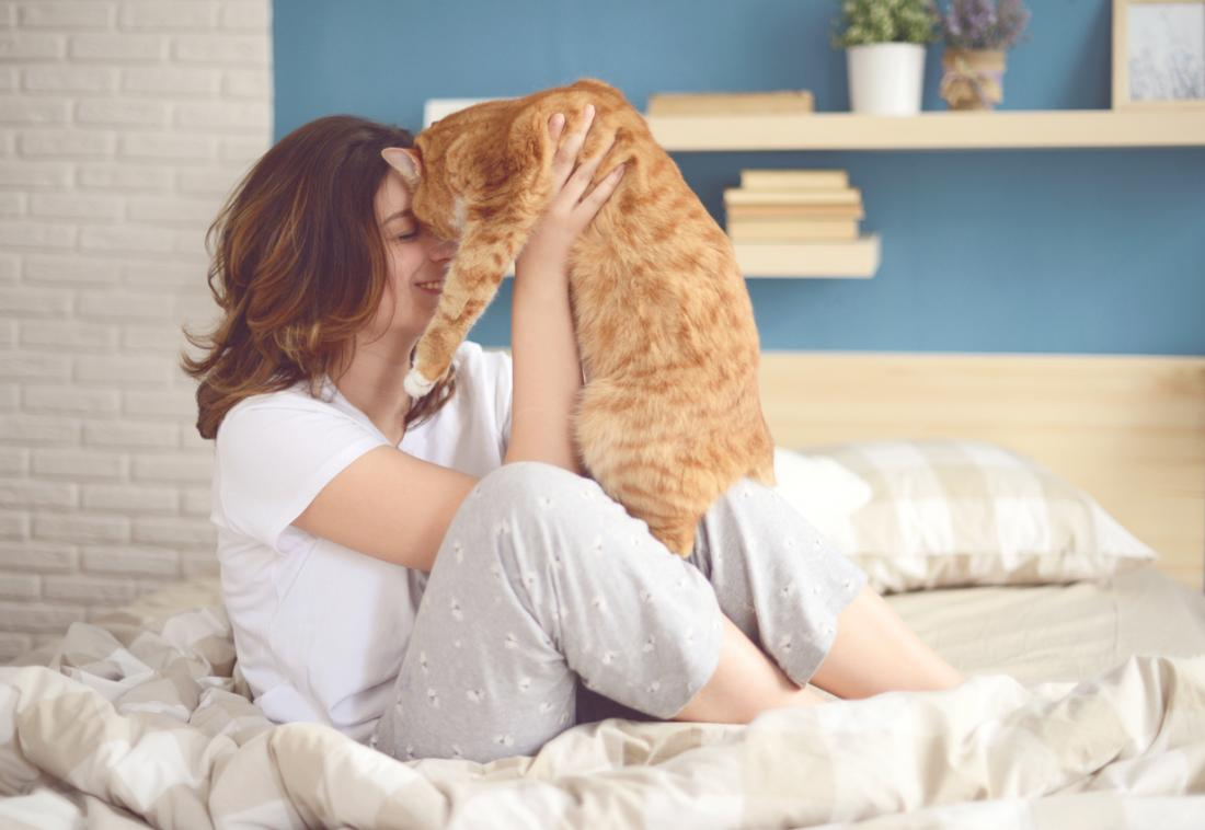 a woman in bed cuddling her cat