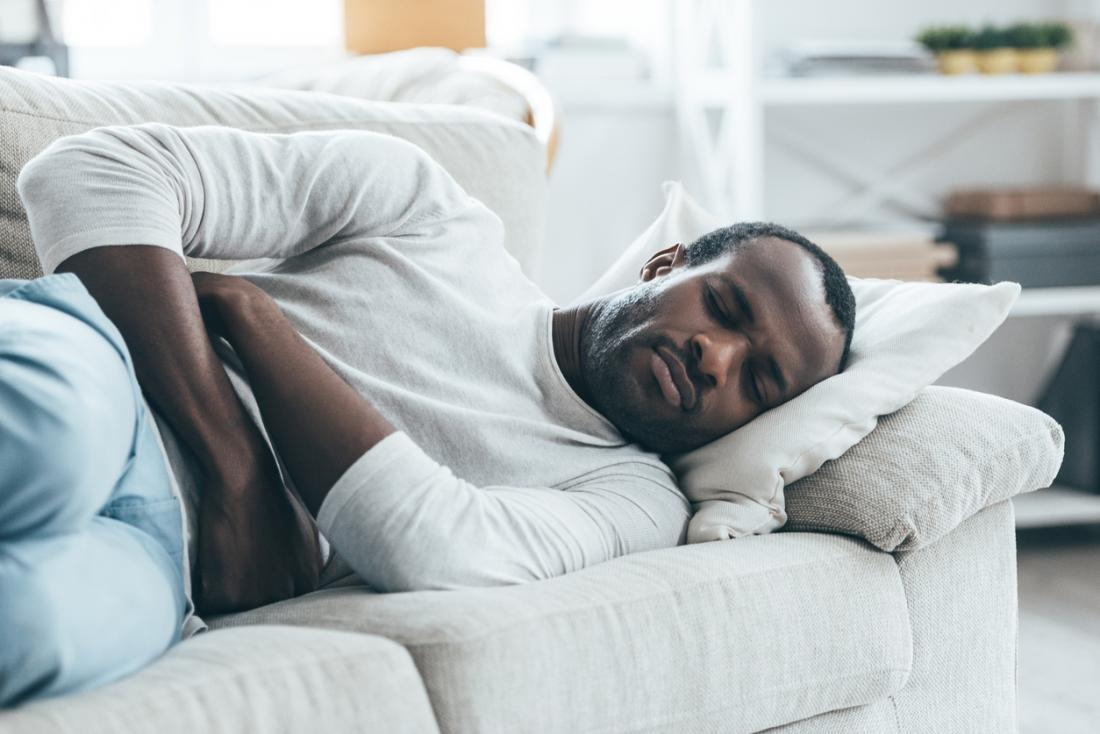 man curled up on the couch with stomach pain