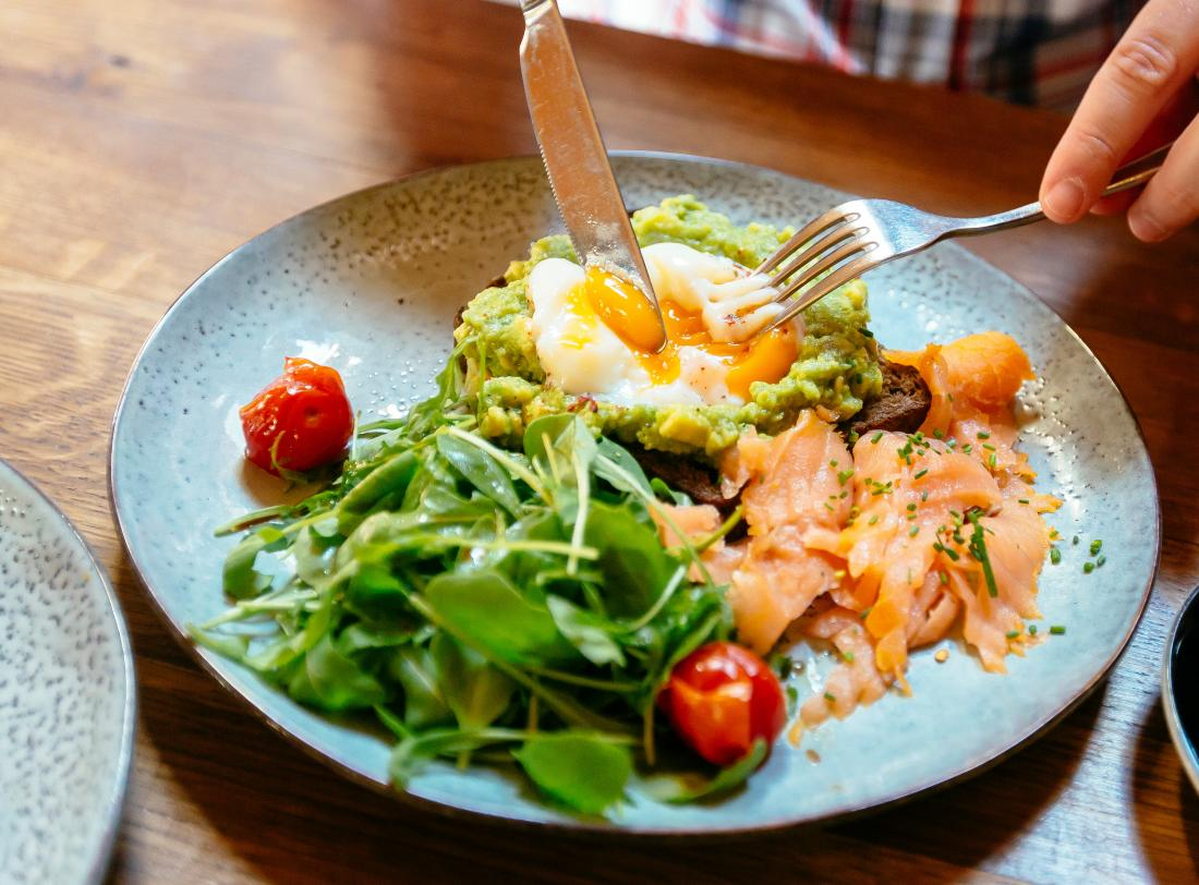 a person eating salmon, eggs and Avocados as part of their ulcerative colitis diet plan