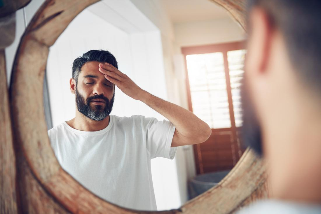 Tired man looking into mirror