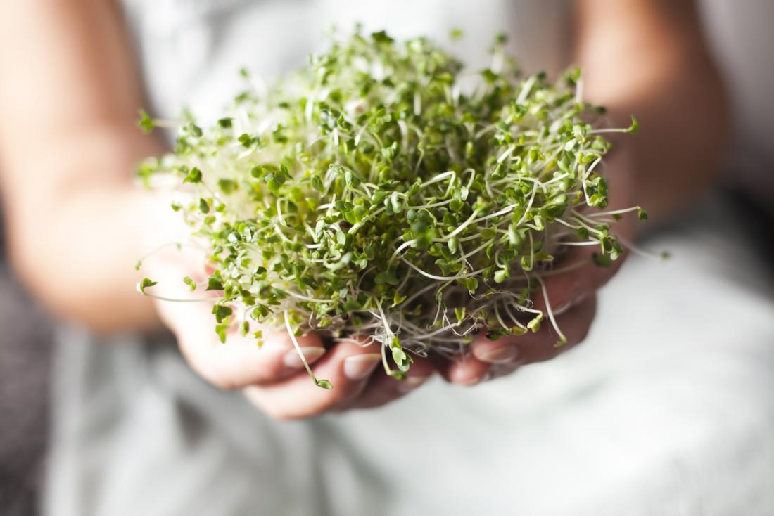 a woman holding broccoli sprouts