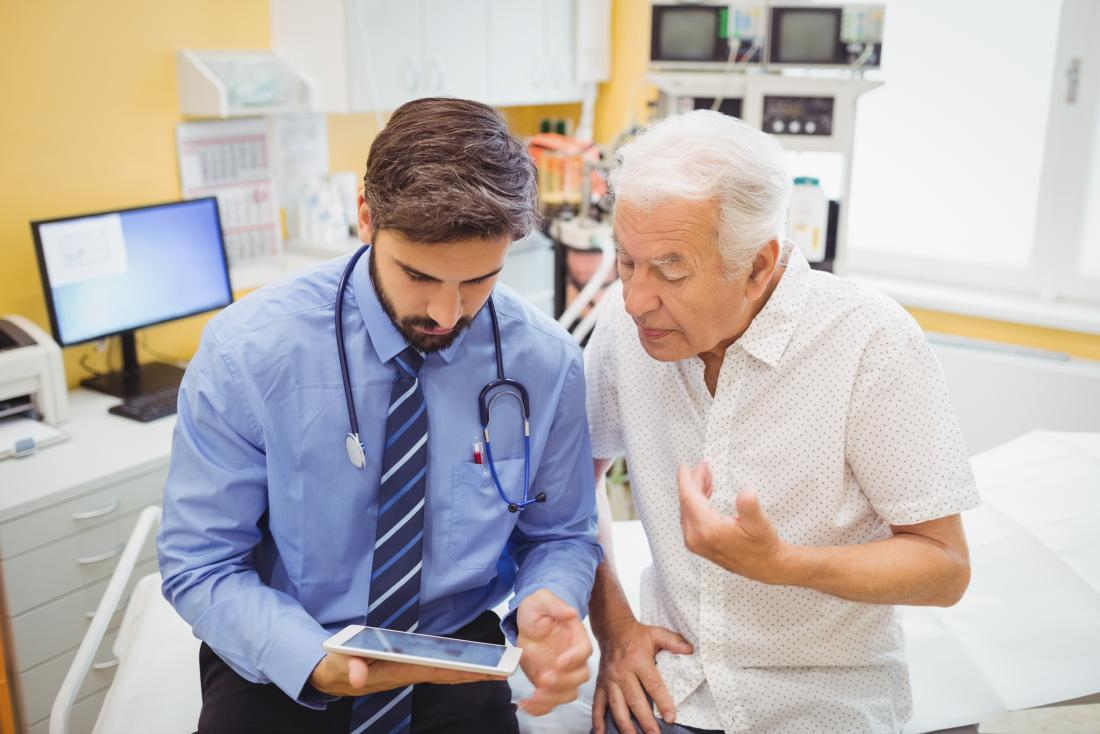 Senior male patient looking at tablet with young doctor