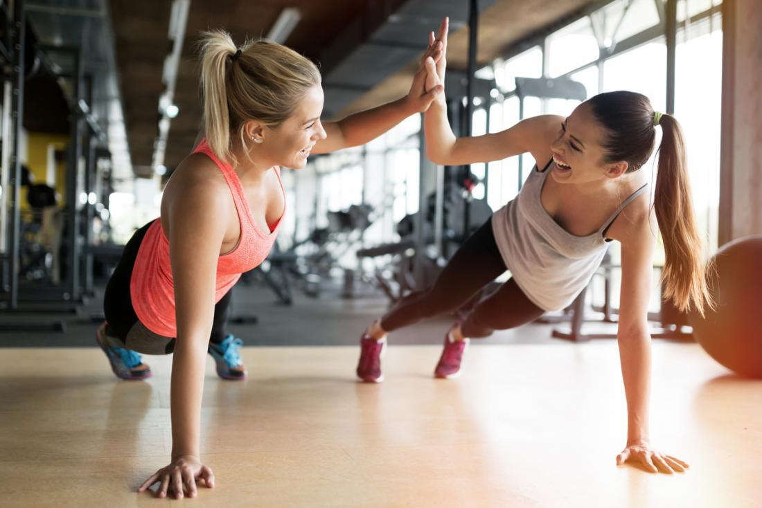 two women doing a high five while doing a plank