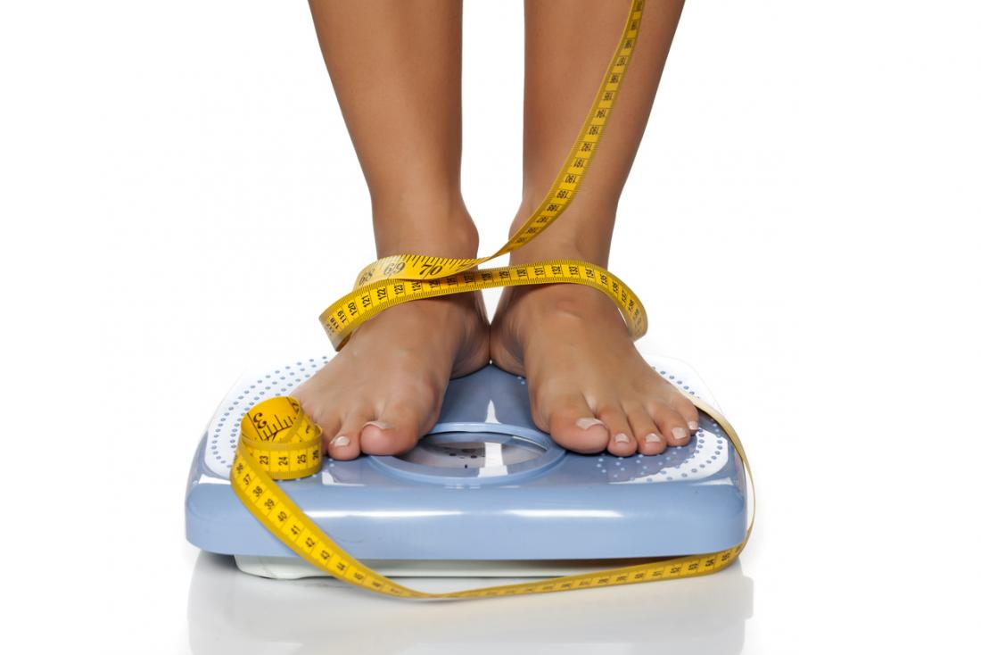 a woman on scales with a tape measure