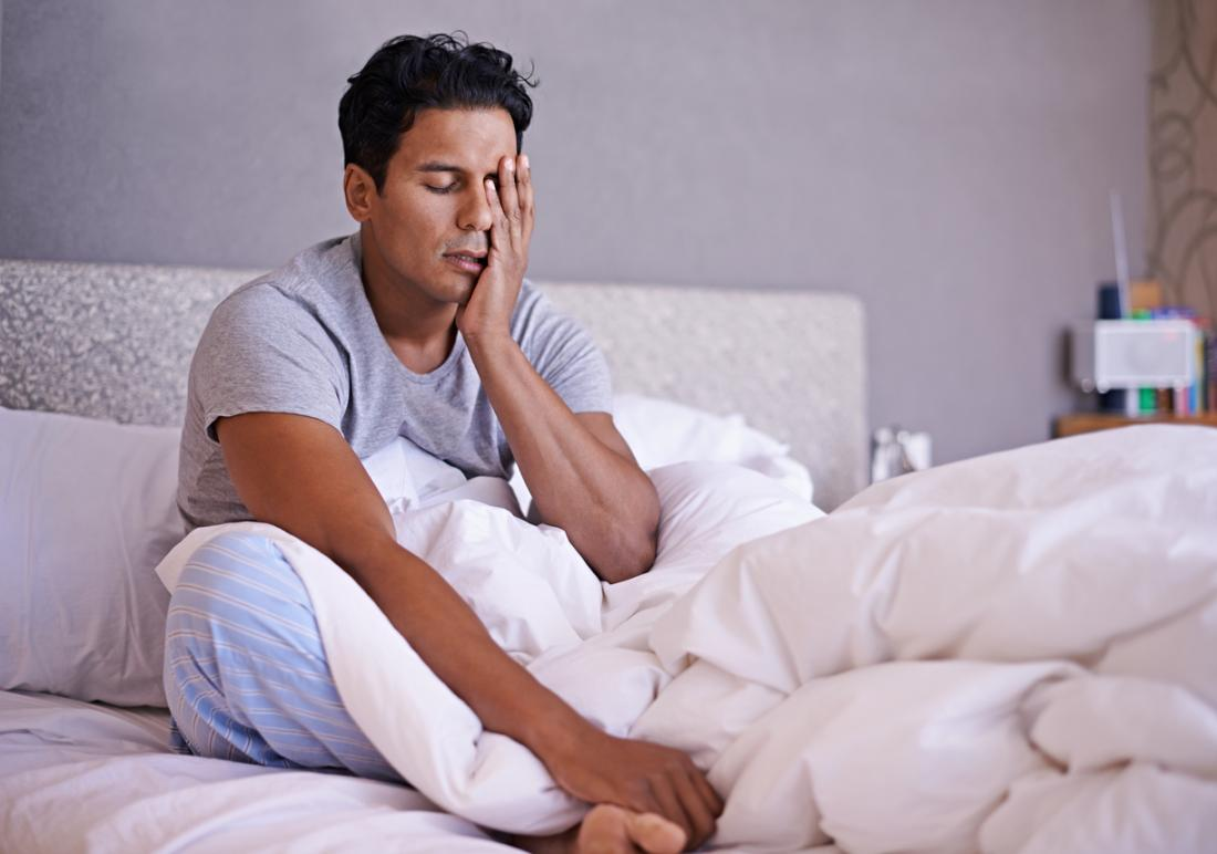 man waking up groggy in bed