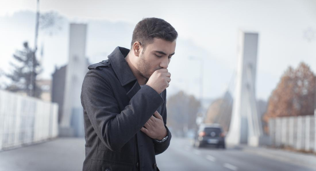 Man coughing in street.